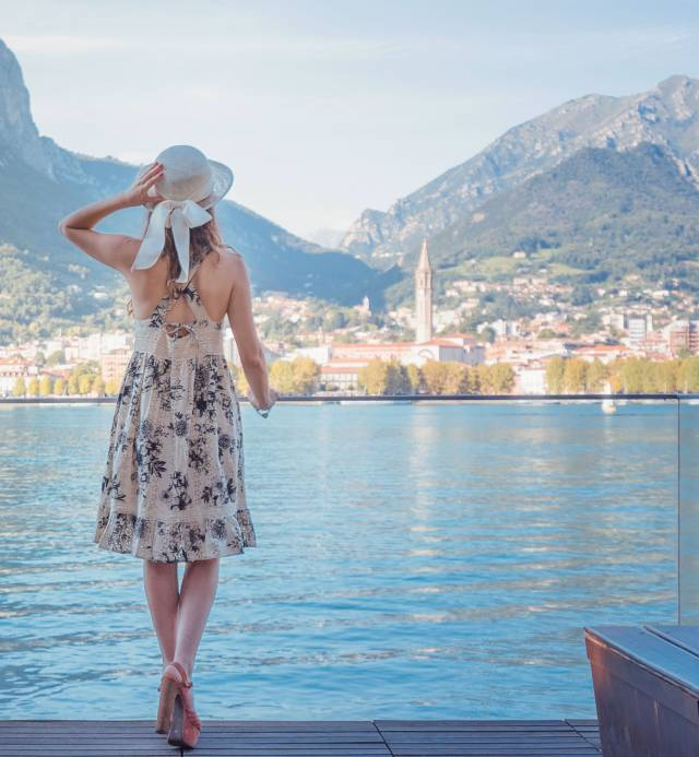 A girl with a hat looking at Lake Como and Lecco city from Malgrate in a sunny day